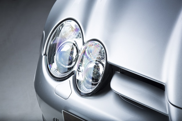 Closeup shot of a headlight of a silver car