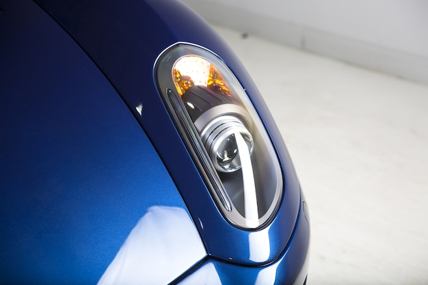 Colpo del primo piano dei fari di una moderna automobile blu