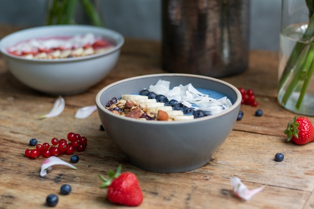 Closeup shot of healthy smoothie bowls with fruits and granola