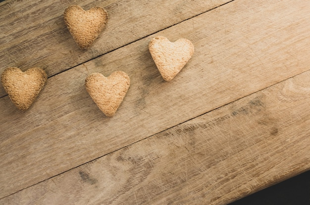 Closeup shot of hearth shaped cookies on wooden background