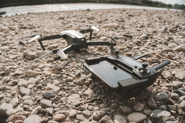 Closeup shot of a high-tech drone and its' remote control device on gray pebbles
