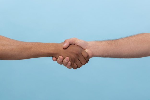 Closeup shot of human holding hands isolated on blue