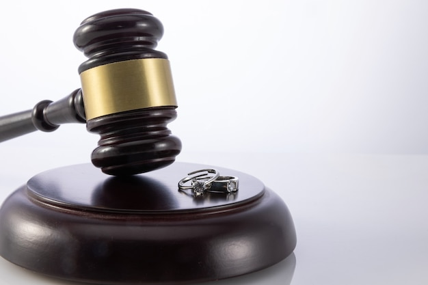 Closeup shot of the judge's gavel with wedding rings - concept of divorce