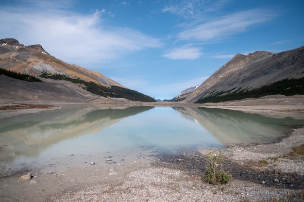 Primo piano di un lago circondato da colline rocciose