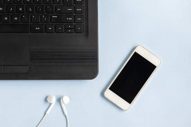 Colpo del primo piano di un laptop, smartphone e auricolari su una superficie azzurra