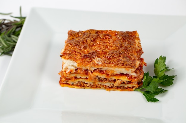 Closeup shot of lasagna on a white plate