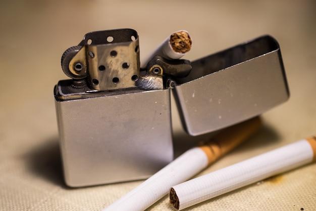 Colpo del primo piano di un accendino e sigarette - smettere di fumare concetto