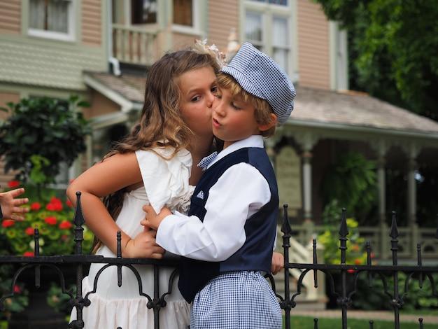 Colpo del primo piano di una bambina che bacia un ragazzo sulla guancia
