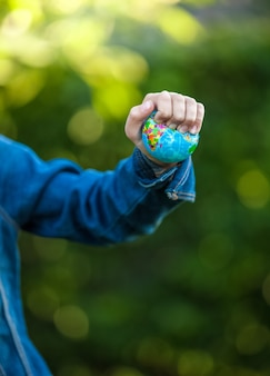 Closeup shot of little girl squeezing earth globe at hand