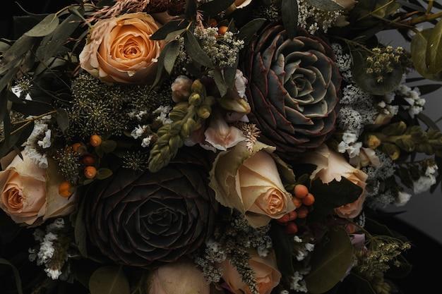 Colpo del primo piano di un lussuoso bouquet di rose arancioni e marroni su fondo nero