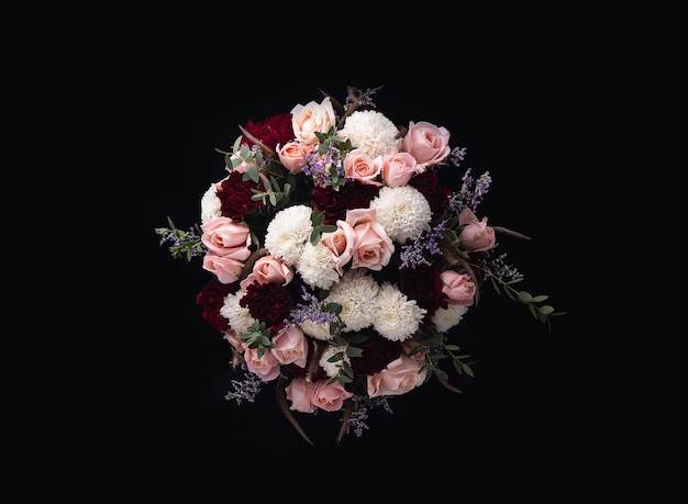 Closeup shot of a luxurious bouquet of pink roses and white, red dahlias on a black background