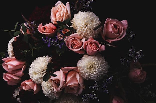 Colpo del primo piano di un lussuoso bouquet di rose rosa e dalie bianche e rosse su fondo nero
