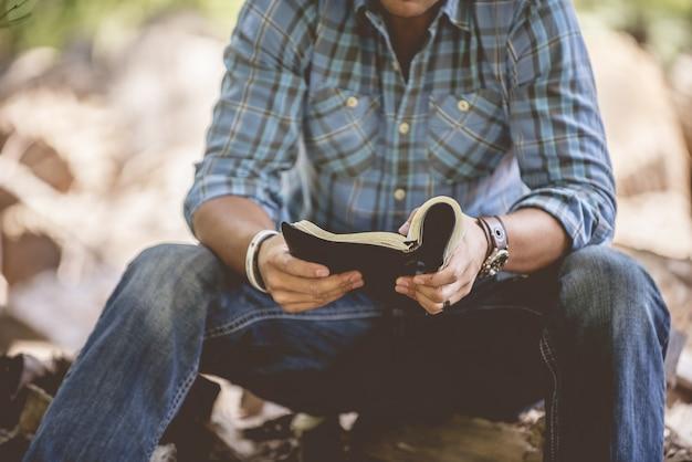 Colpo del primo piano di un maschio in abbigliamento casual che legge la sacra bibbia su uno sfondo sfocato