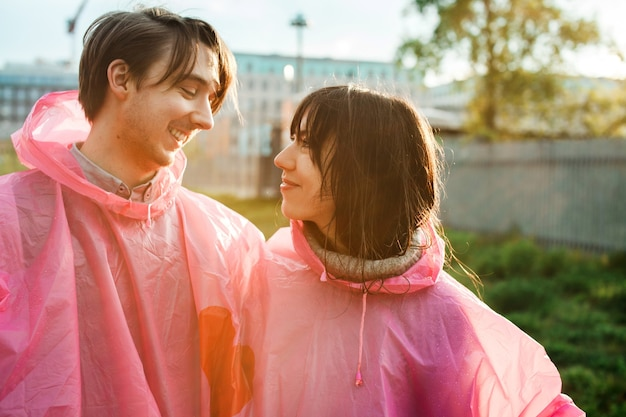 Closeup shot of a male and a female in pink plastic raincoats looking at each other romantically