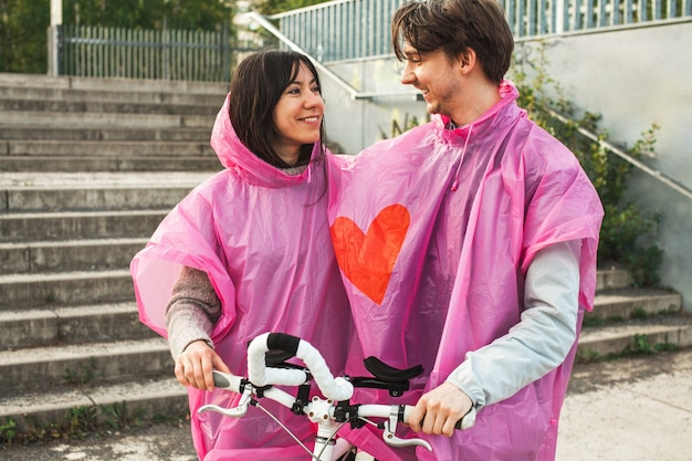 Closeup shot of a male and a female sharing a pink plastic raincoat with a red heart in the center