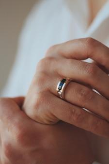 Colpo del primo piano di un maschio in un abito formale che indossa un anello d'oro