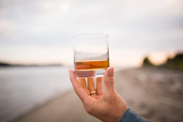 Primo piano di una mano maschile che tiene un bicchiere di whisky