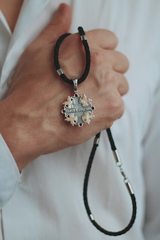 Closeup shot of a male holding a charm necklace with a silver pendant and a black cord