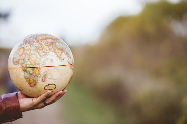 Closeup shot of a male holding a desk globe with a blurred background