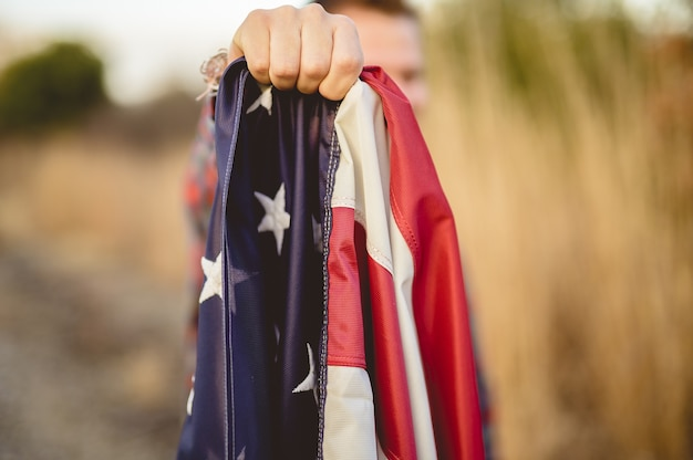 Closeup shot of a male holding the flag of the united states