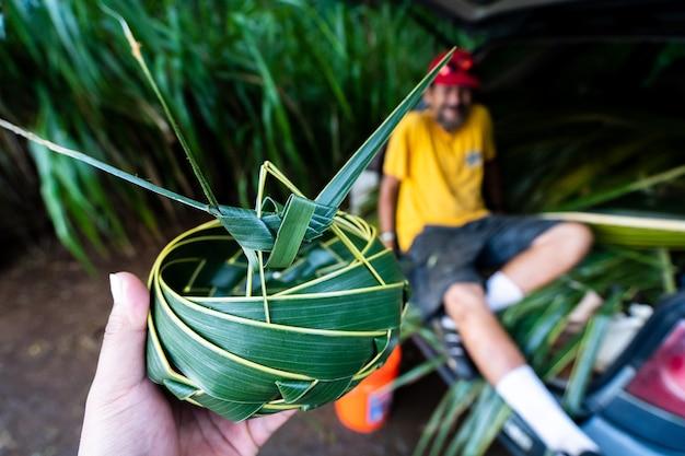 Colpo del primo piano di un maschio che tiene un piatto fatto di foglie