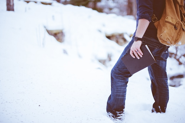Colpo del primo piano del maschio in piedi nella neve con uno zaino e che tiene la bibbia