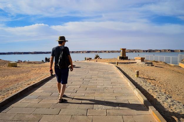 Colpo del primo piano di un maschio che cammina su una strada vicino al mare in una giornata di sole
