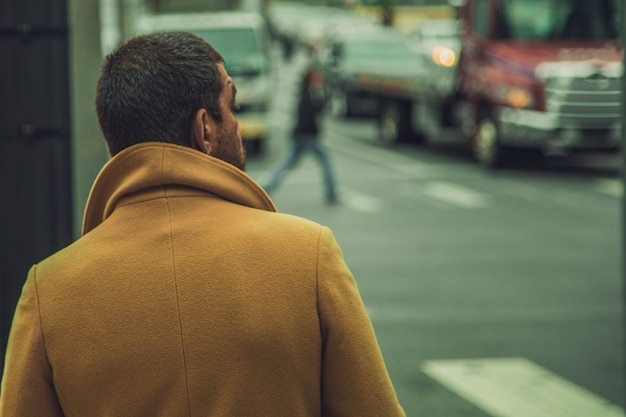 Closeup shot of a male wearing bright brown coat standing near the street