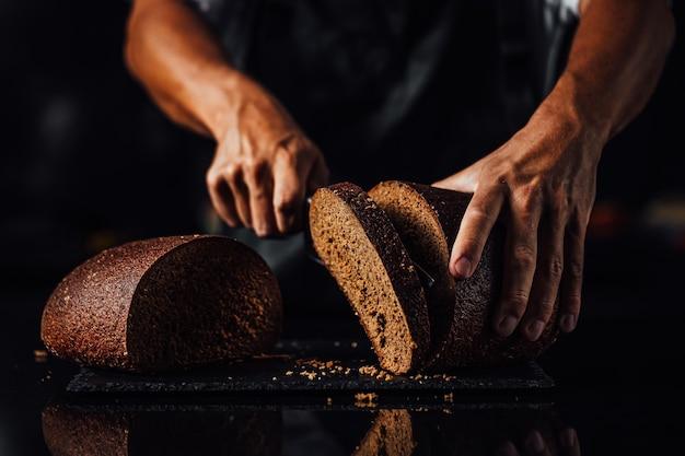 Primo piano di un uomo che taglia pane integrale su una tavola di pietra