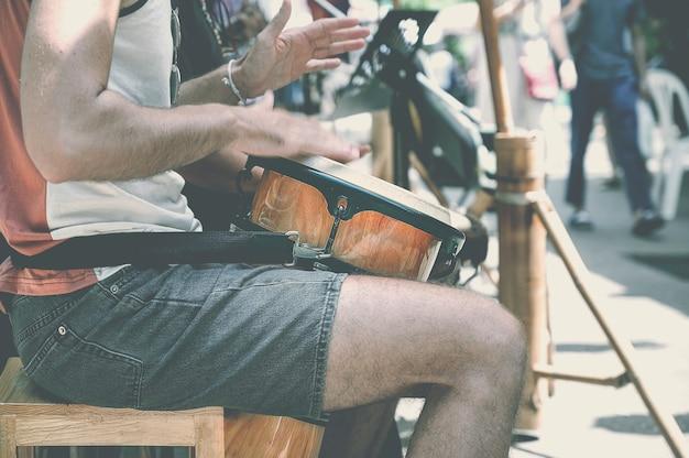 Closeup shot of man hand playing a drum outdoors.