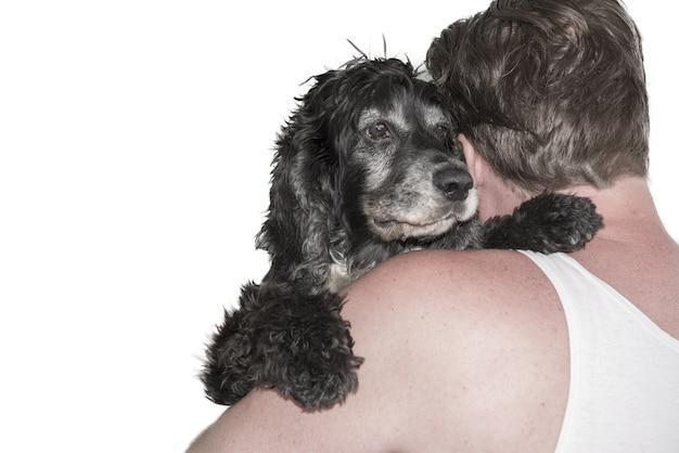 Colpo del primo piano di un uomo che abbraccia un cane nero dietro su bianco