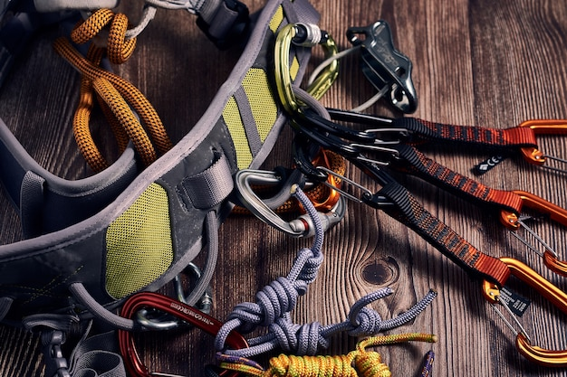 Closeup shot of many colorful climbing carabiners and knots on a wooden surface