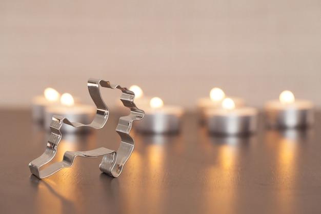 Colpo del primo piano di una decorazione di cervo in metallo e candele sfocate sullo sfondo