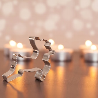 Closeup shot of metal deer decoration with blurred small candles on the background
