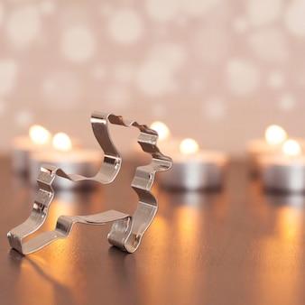 Colpo del primo piano della decorazione dei cervi del metallo con le piccole candele sfocate sui precedenti