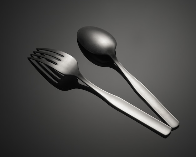 Closeup shot of a metal fork and a spoon isolated on a gray table