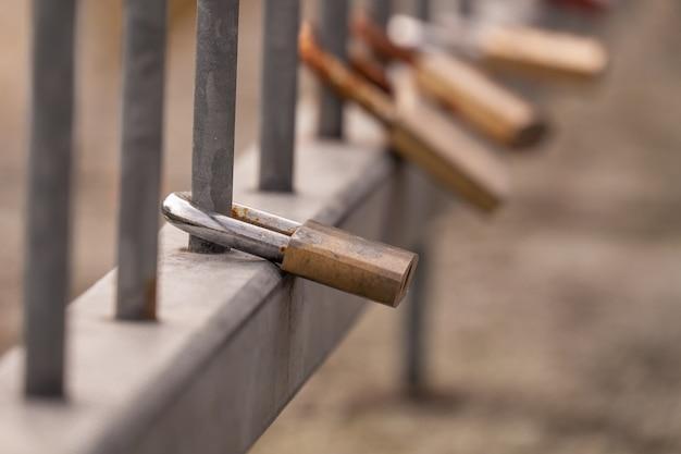Colpo del primo piano di lucchetti in metallo con un cuore appeso a una recinzione