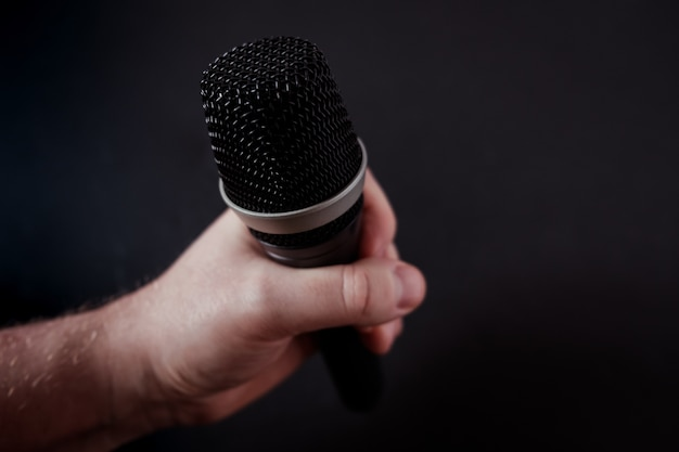 Closeup shot of a microphone in the hand of a person on black