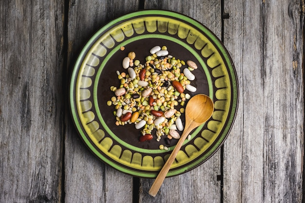 Closeup shot of mixed beans in a plate with a wooden spoon