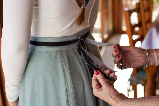 Colpo del primo piano della madre che aiuta la sposa a organizzare l'abito da sposa