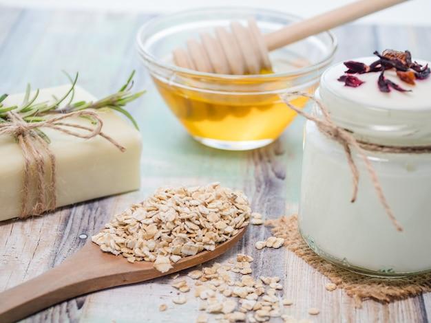 Closeup shot of natural skincare product ingredients: yogurt, oat flakes, natural soap, and yogurt