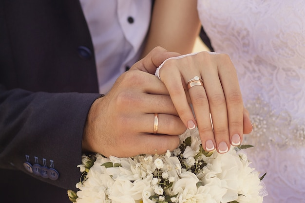 Closeup shot of newlyweds holding hands and showing the wedding rings