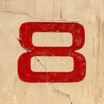 Closeup shot of the number 8 painted on a wall in red