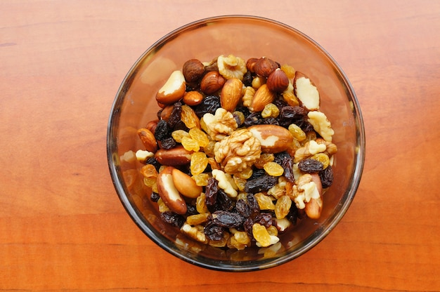 Closeup shot of nuts and raisins mix in a bowl on a wooden surface