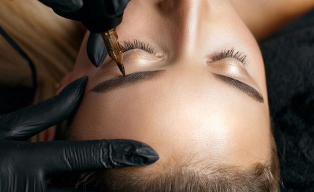 金髪の女性に永久的な眉メイクを適用する黒い手袋の美容師のクローズアップショット。テキスト用のスペース
