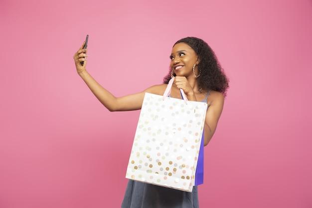 ショッピングバッグで自分撮りをしている美しいアフリカ系アメリカ人の女の子のクローズアップショット