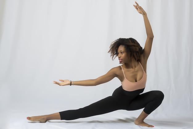 白い表面にストレッチポーズをとる美しいダンサーの女性のクローズアップショット