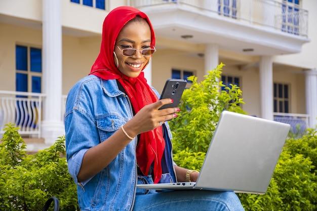 밖에 앉아 있는 아름다운 젊은 아프리카 여성의 클로즈업 샷