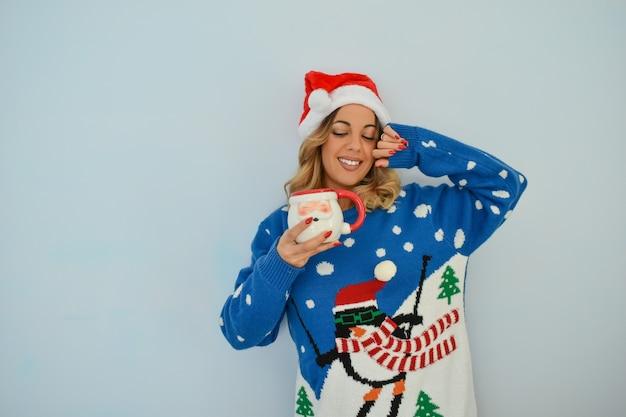 クリスマスのドレスとサンタカップを保持している帽子を身に着けている美しい若い女性のクローズアップショット