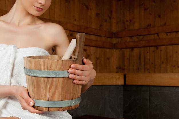 Снимок крупным планом красивой молодой женщины, держащей ведро в сауне